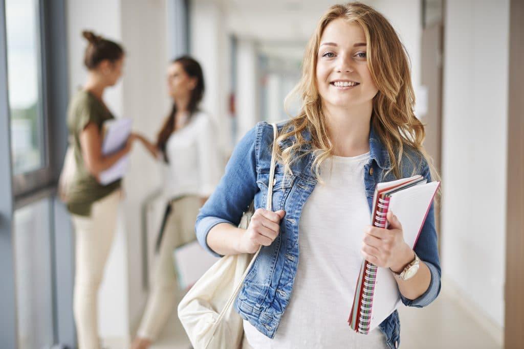 תמונה של סטודנטית עם מחברות ביד