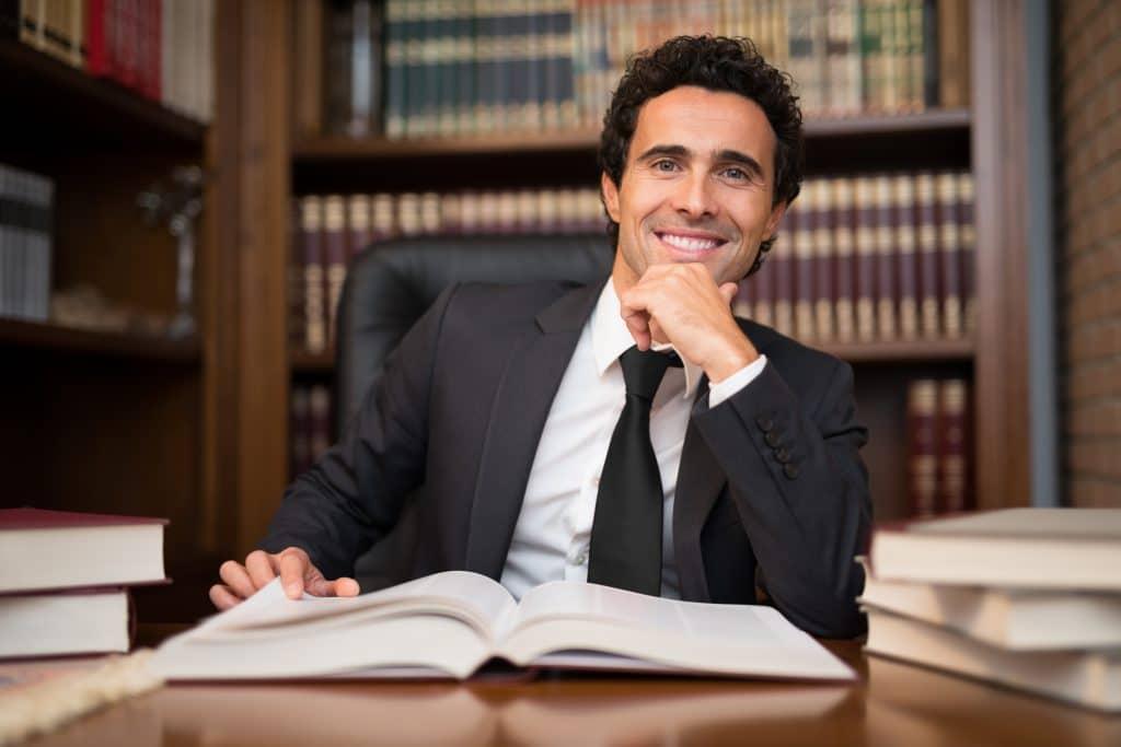 תמונה של עורך דין מצליח מסתכל למצלמה עם ארון ספרי משפט מאחוריו