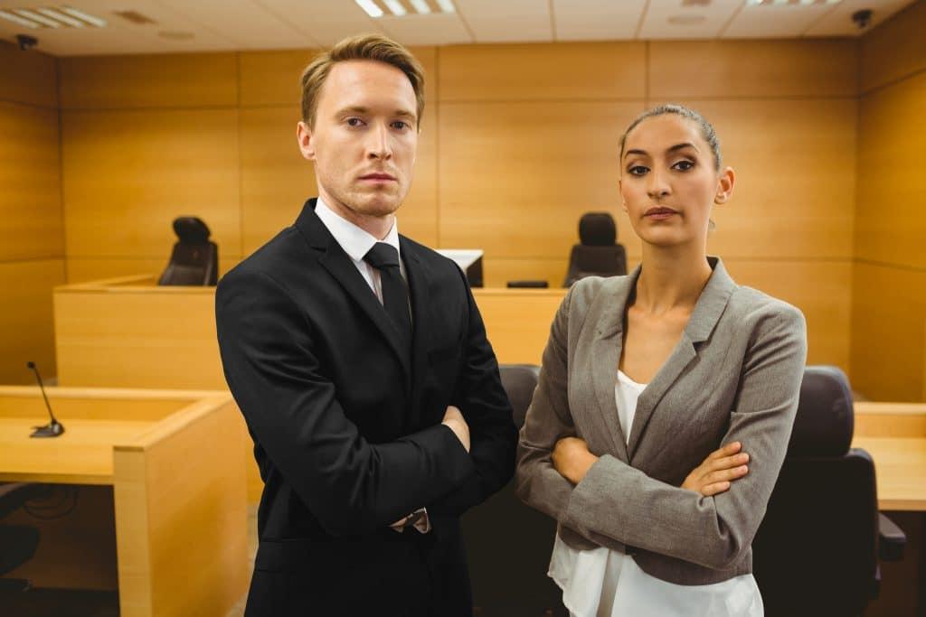 תמונה של שני עורכי דין באולם בית המשפט מסתכלים למצלמה