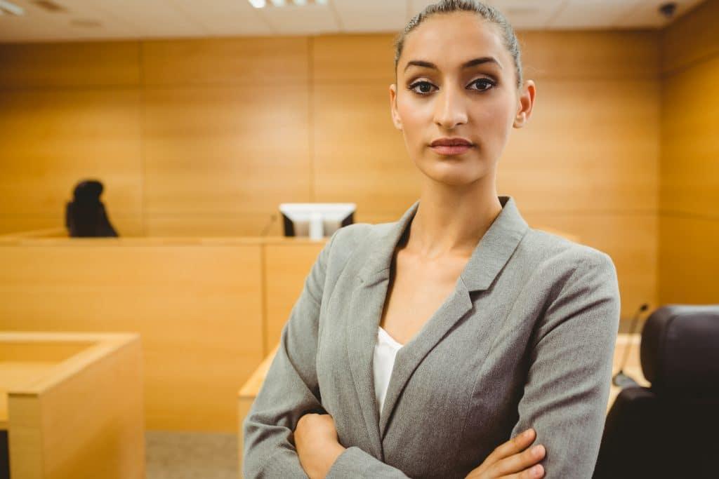 תמונה של עורכת דין באולם בית המשפט מסתכלת למצלמה