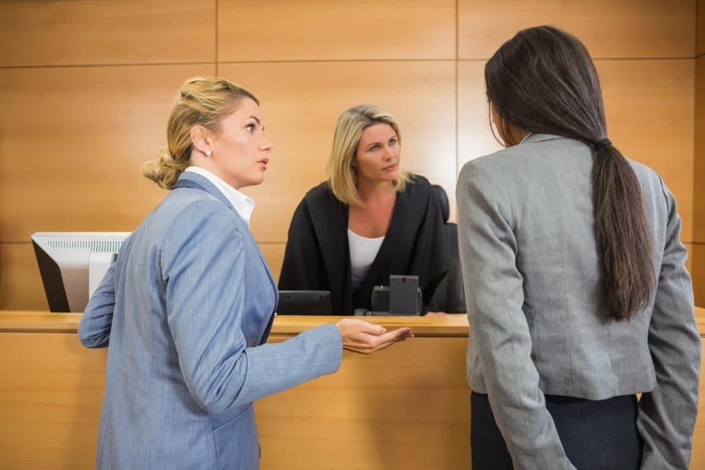 תמונה של שופטת עם עורכות דין של שני הצדדים באמצע חילופי דברים