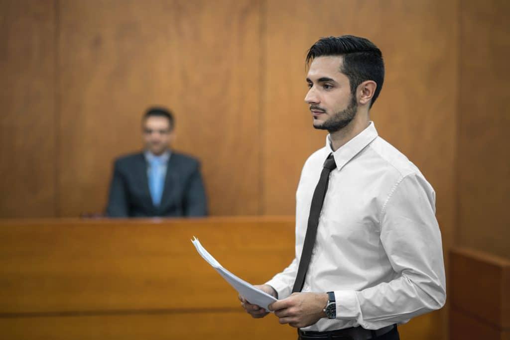 תמונה של עורך דין צעיר מגיש מסמכים באולם בית המשפט